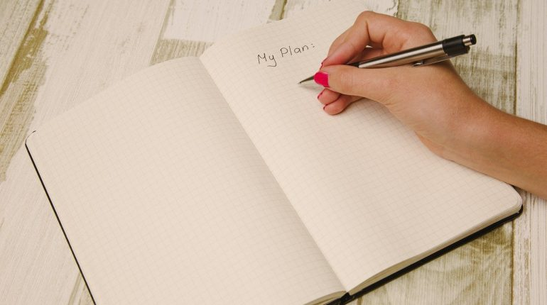 woman writing her plan in a notebook